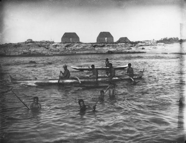 Men and boys fish in a bay, some in outrigger canoes, others in the water with snared fish. Beyond is a rocky shore with three thatched houses. This photo was taken by Francis Sinclair in 1885.