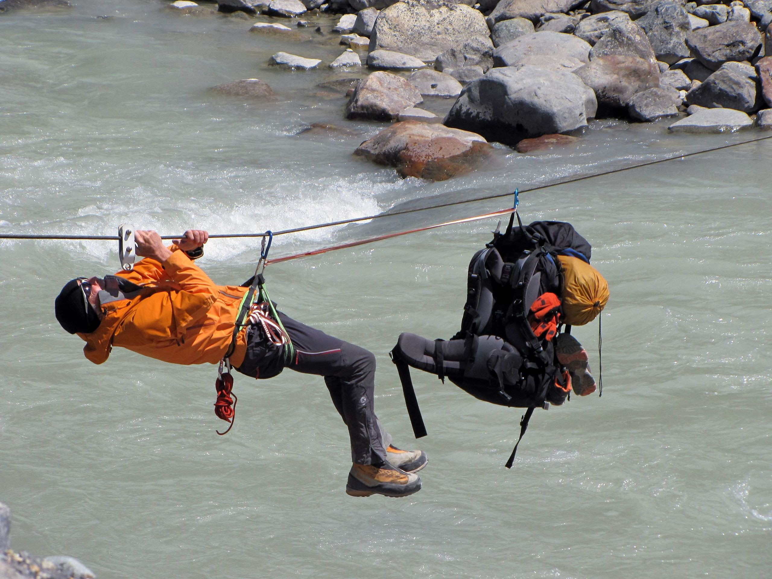 Climber uses tyrolean traverse to cross a Rio Fitz Roy in Argentina Image source