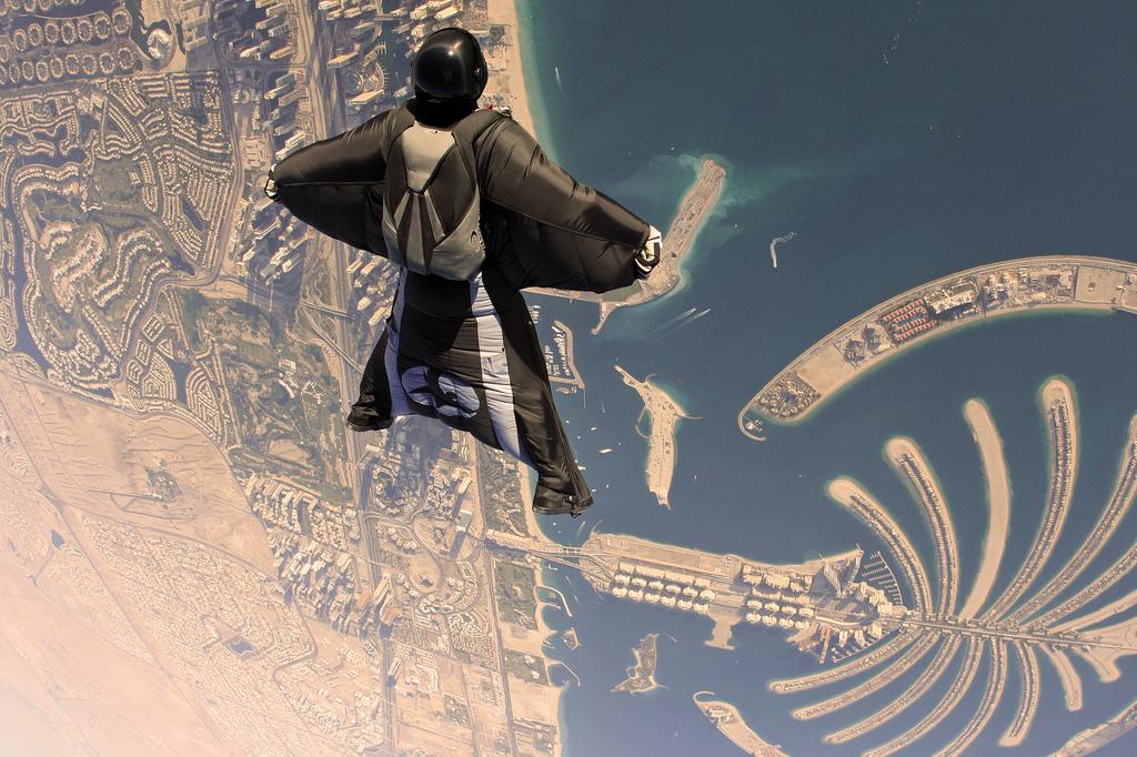A wingsuit flyer over Palm Islands, Dubai - Image source