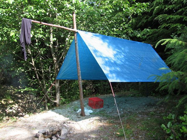 An improvised fly tent using a tarpaulin