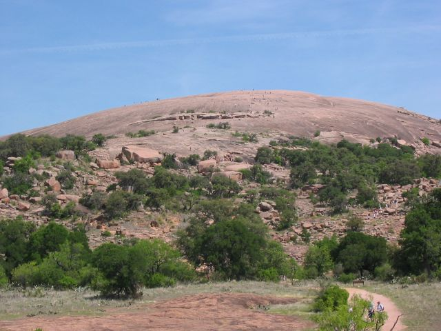 Enchanted Rock as viewed from the trail leading to the summit. People climbing on the summit (visible as dots) give an idea of the scale of the granite rock.