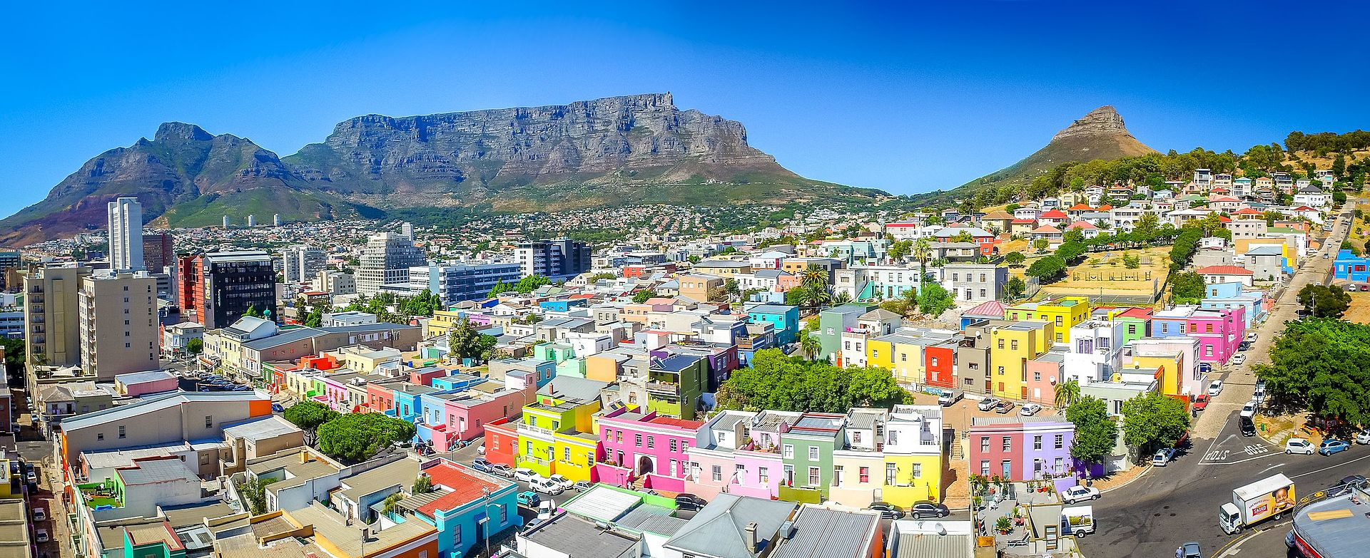 Bo-Kaap area of Cape Town with its distinctive pastel-colored houses in the foreground with the city centre to the left and Table Mountain in the background - Author: SkyPixels - CC BY-SA 4.0