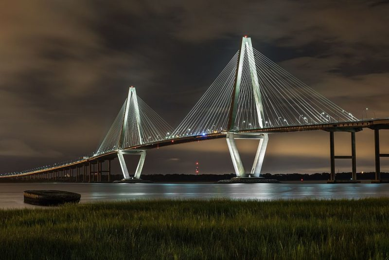 Arthur Ravenel Jr. Bridge (also known as the Cooper River Bridge) at night, looking northwest from Point Pleasant, South Carolina – Author: Juliancolton – CC BY-SA 4.0
