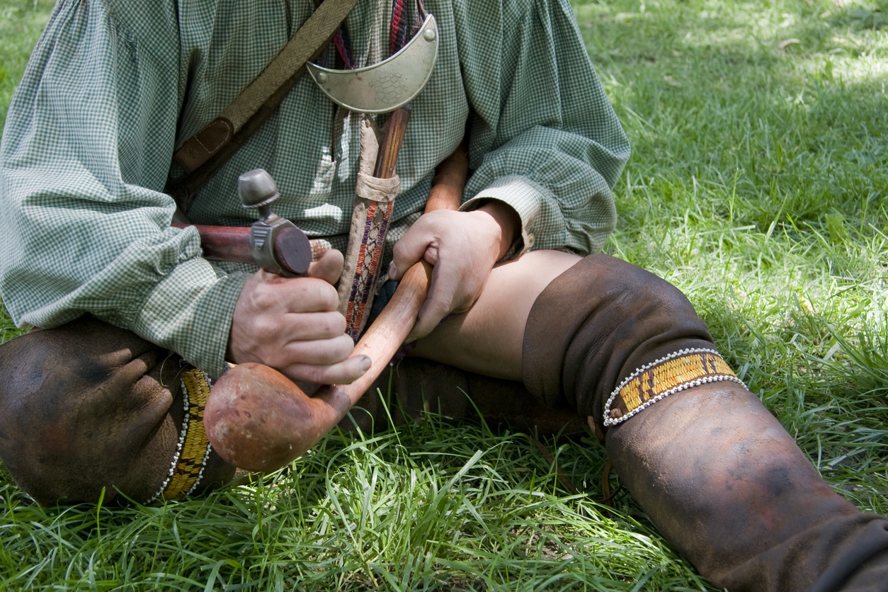 A reenactor portraying an Iroquois Indian from the New York Senaca tribe.  He is using his Tomahawk to carve his war club.  The war club was used as the primary weapon by the Iroquois during the French and Indian war.