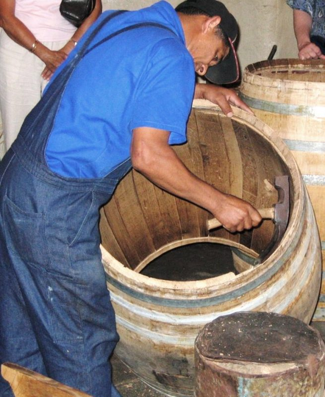 A cooper readies or rounds off the end of a barrel using a cooper's hand adze – Author: Soerfm – CC BY-SA 2.0
