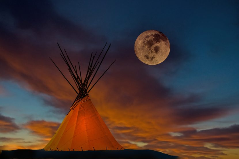 A prairie First Nation teepee with interior light at sunset. Full moon
