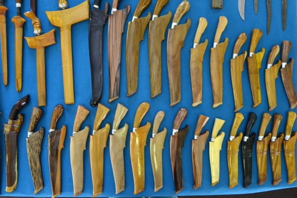 A variety of parangs in sheaths.