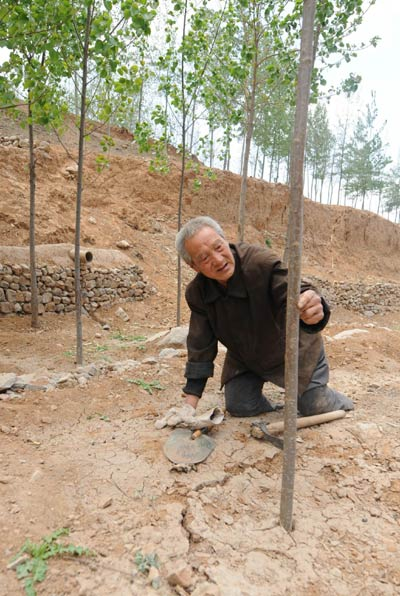 He uses crutches, crawls through ditches, and pulls himself up hills – Photo Credit: Xinhua