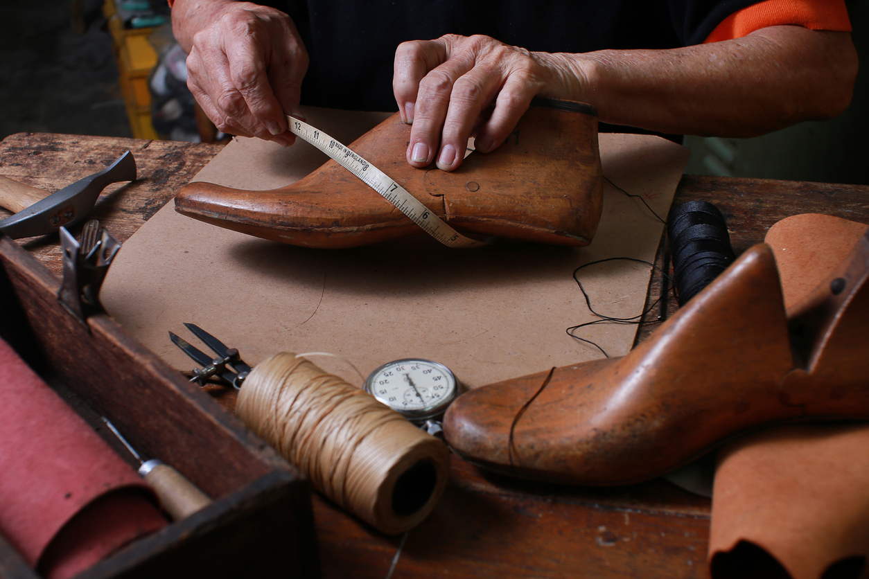 Shoemaker measuring a shoe with measure tape in workshop