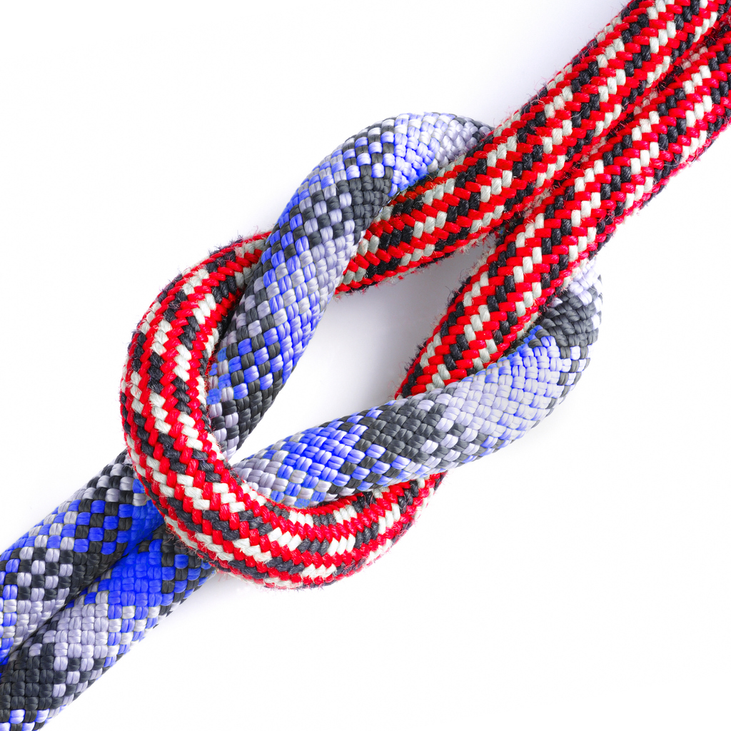 Red and blue climbing ropes connected in a reef knot or square knot.
