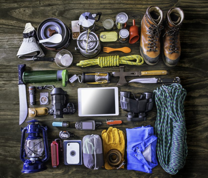 Top view of travel equipment and accessories for mountain hiking trip on wood floor. Space for text into digital tablet.