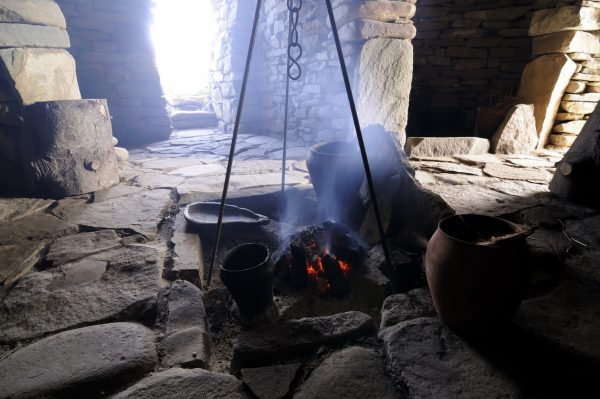 A smouldering peat fire inside a reconstructed iron age house.