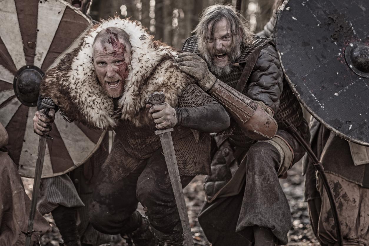 A hoard of Weapon wielding bloody viking warriors on a winter battlefield forest