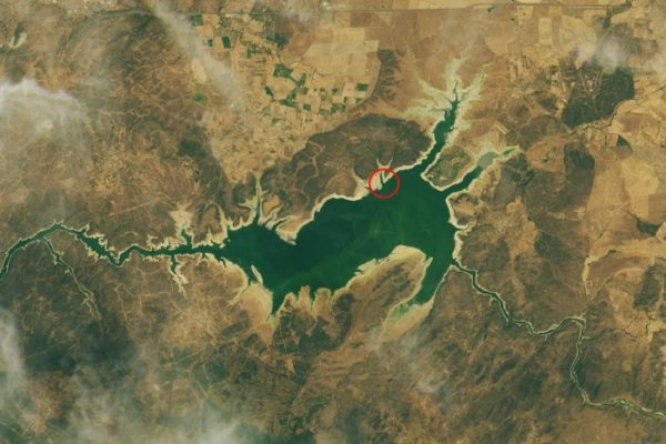 A satellite image of the Valdecanas Reservoir from July. The red ring marks the Dolmen of Guadalperal. NASA Earth Observatory