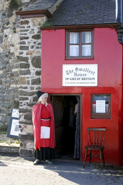 A lady dressed in welsh costume can be seen outside the house.