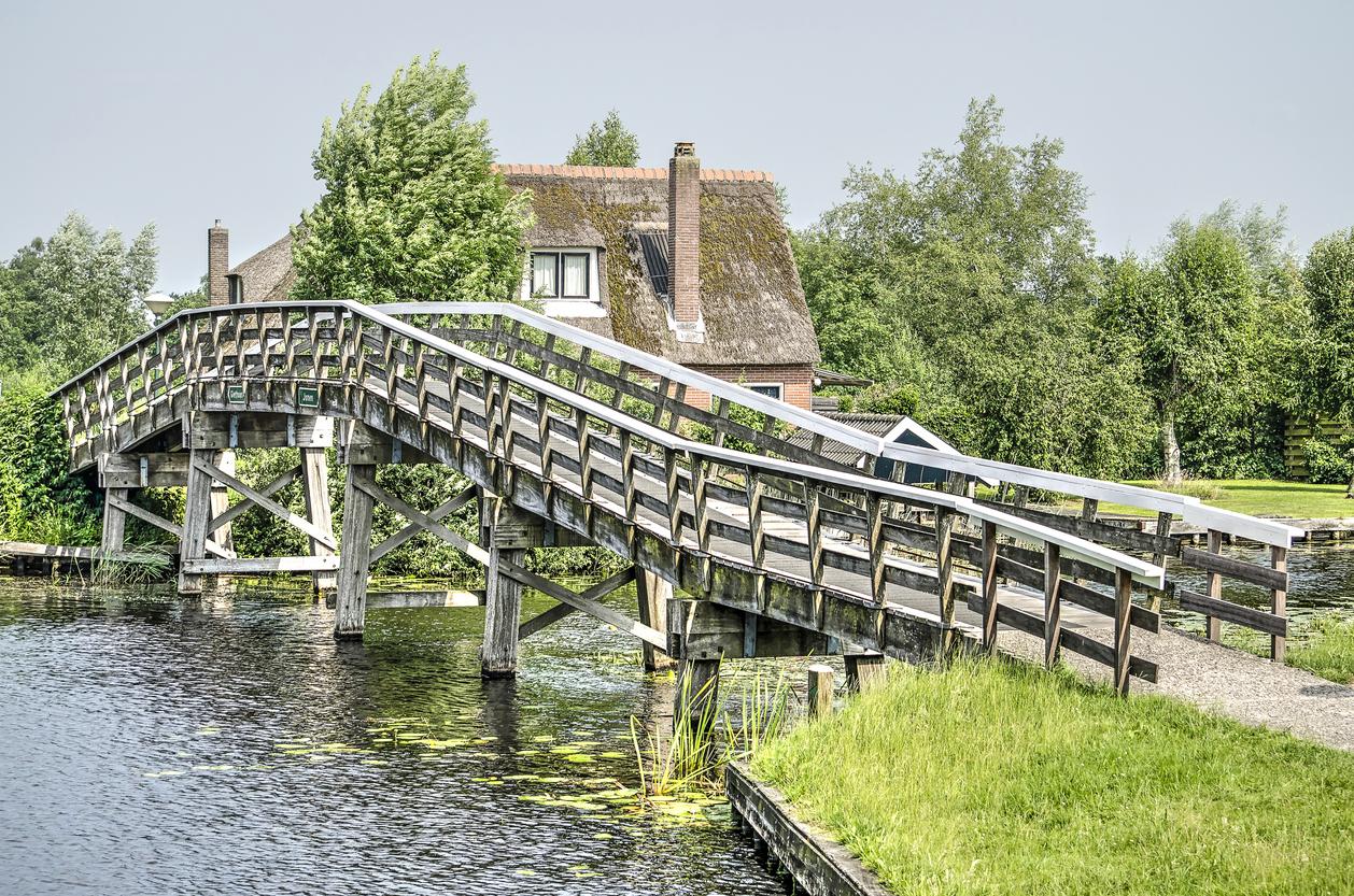 Dwarsgracht, The Netherlands, June 9, 2018: Long woonden pedestrian bridge across a canal in Dwarsgracht