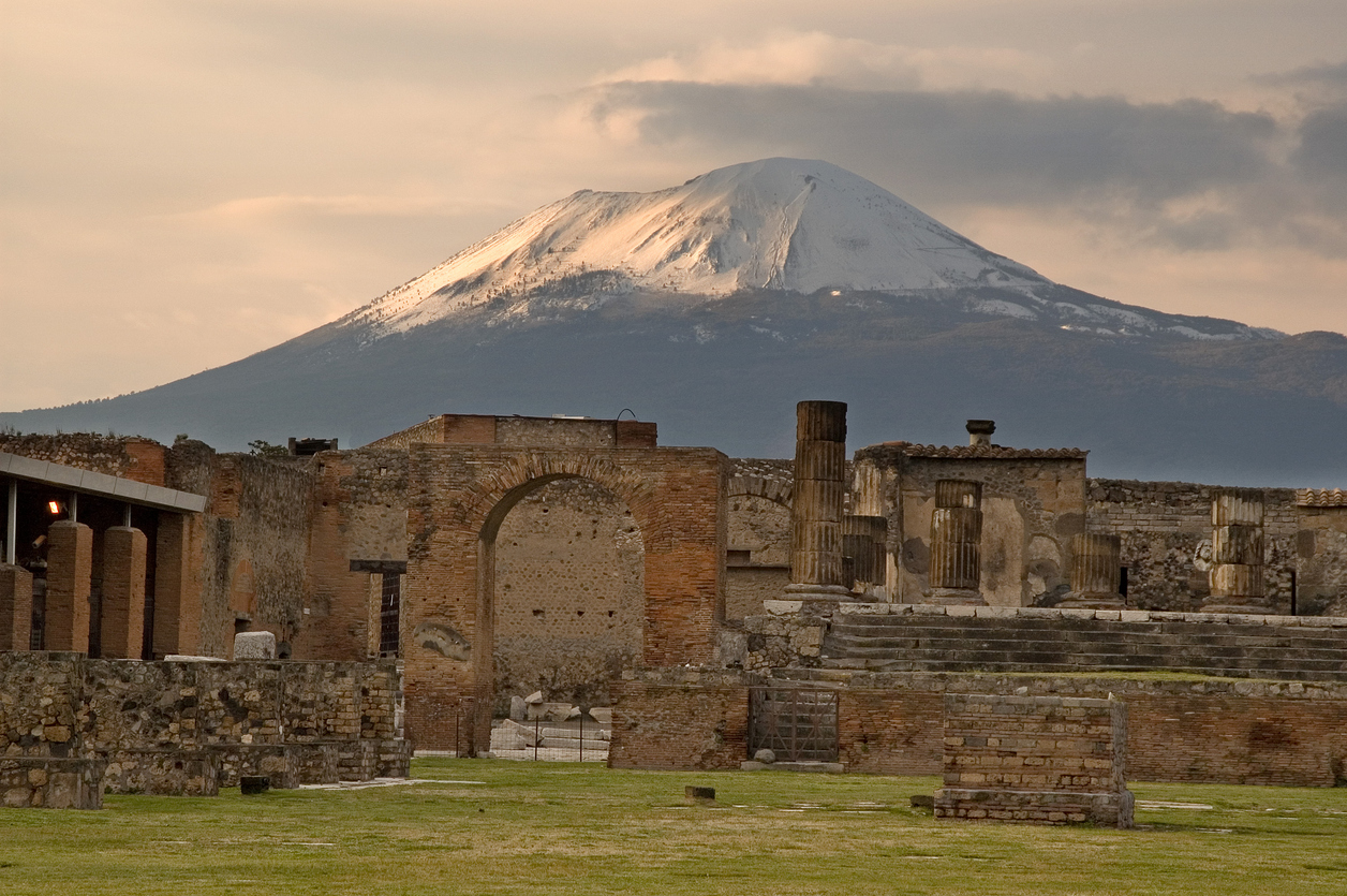 The sun begins to set on the snow capped Mount Vesuvius still overlooking Temple of Jupiter standing in the forum of Pompeii